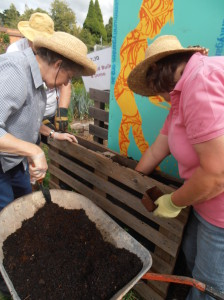 Kathi filling the weedmat lined pallet with potting mix in preparating for planting up.