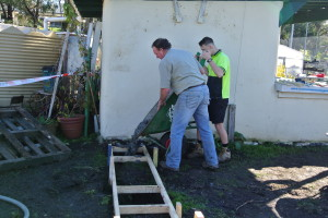 Phil Marshall helps Jack empty his barrow load of concrete.